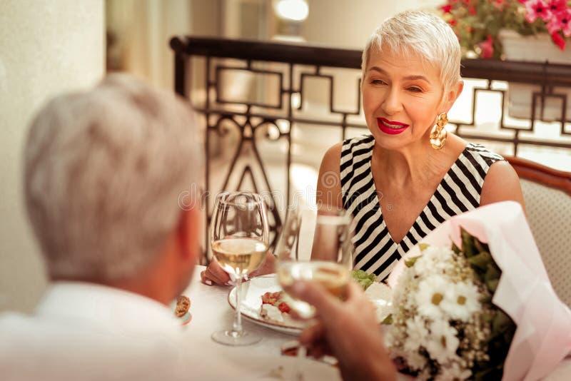 Blonde-haired vrouw die terwijl het hebben van romantisch diner met echtgenoot glimlachen stock fotografie