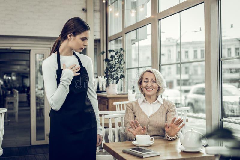 Blonde-haired vrouw die van de koffie houden niet die zij in cafetaria heeft gekregen stock afbeeldingen