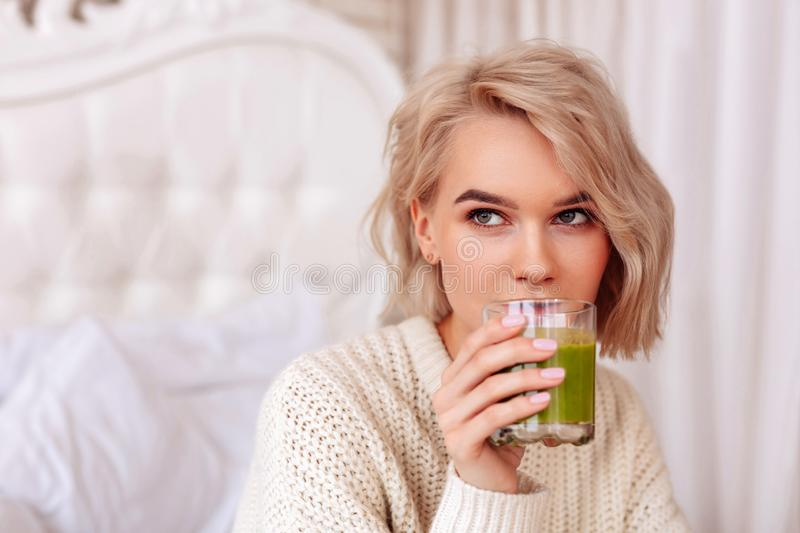 Blonde-haired woman drinking healthy green juice in bedroom stock photo