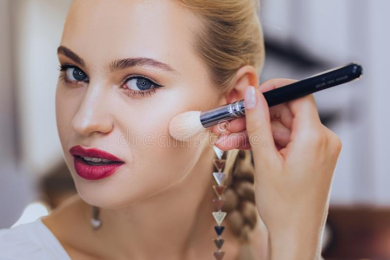 Blonde-haired woman with red lips holding makeup brush. Makeup brush. Blonde-haired appealing stylish woman with red lips holding makeup brush stock image