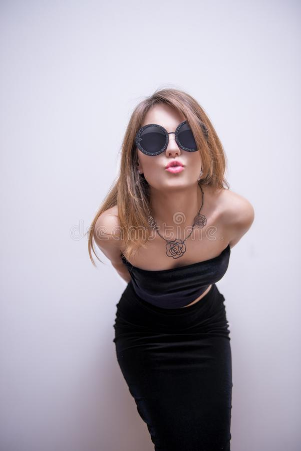 Blonde Haired Woman in Round Black Sunglasses Pouting Behind White Concrete Wall royalty free stock photography