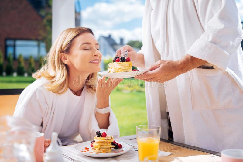 Blonde-haired woman smelling nice warm pancakes with fruits on top royalty free stock photos