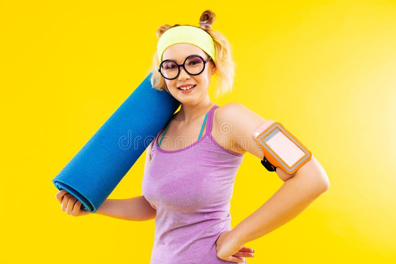 Blonde-haired woman wearing glasses going to yoga class stock photo