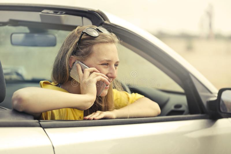 Blonde-haired Woman in Yellow T-shirt Wearing Black Sunglasses Holding Silver Smartphone stock photos