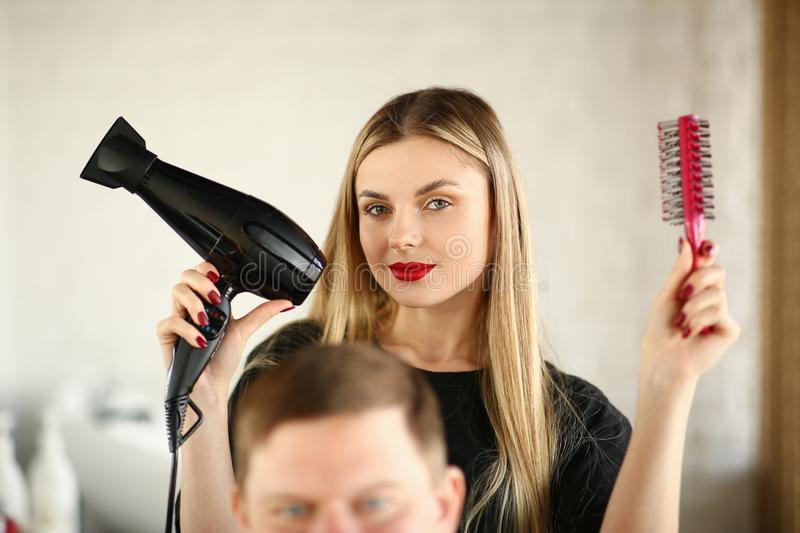 Blonde Hairstylist Showing Blow Dryer and Comb. Woman Hairstylist Using Hairbrush and Hairdryer for Styling Male Haircut in Beauty Salon. Female Stylist Making stock image