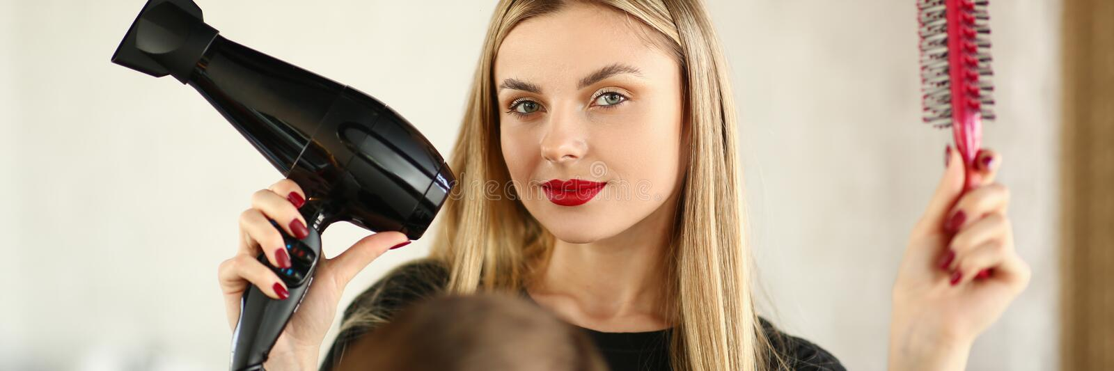 Blonde Hairstylist Showing Blow Dryer and Comb royalty free stock photos