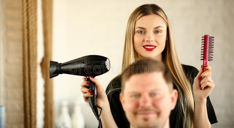 Blonde Hairstylist Using Dryer and Comb for Man stock photography
