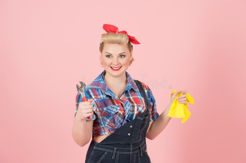 Blonde happy smiled female in pin-up style holding yellow latex gloves and wrench isolated on pastel-pink background. stock photography