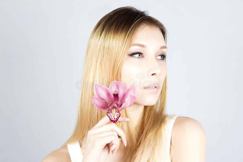 Blonde hermoso atractivo con una flor rosada Mujer con maquillaje permanente imagenes de archivo
