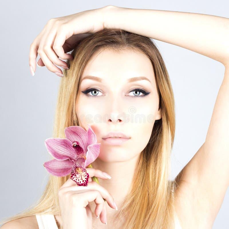 Blonde hermoso atractivo con una flor rosada Mujer con maquillaje permanente Ciérrese encima del retrato de la mujer foto de archivo libre de regalías