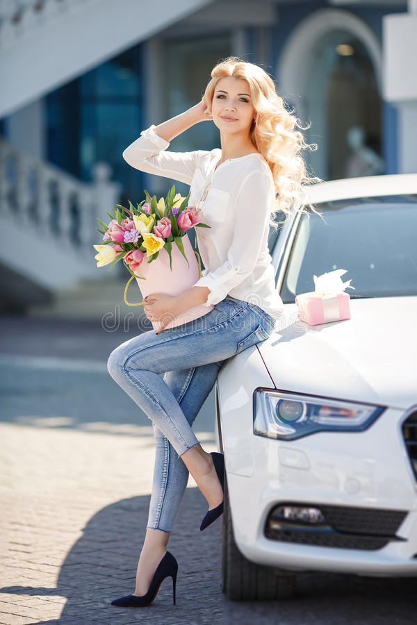 Blonde hermoso con las flores en caja de regalo fotos de archivo