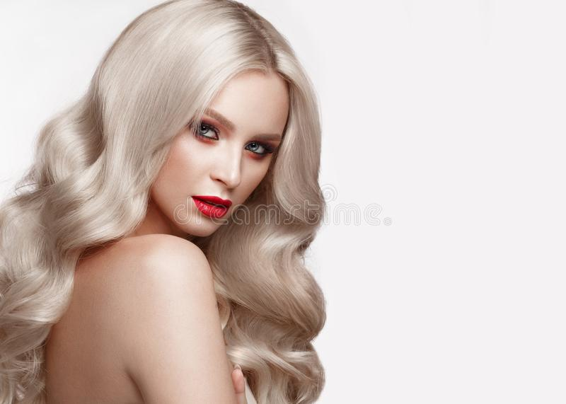 Blonde hermoso de una manera de Hollywood con los rizos, el maquillaje natural y los labios rojos Cara y pelo de la belleza fotografía de archivo libre de regalías
