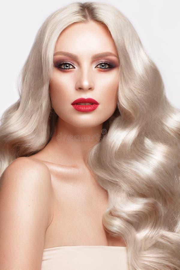 Blonde hermoso de una manera de Hollywood con los rizos, el maquillaje natural y los labios rojos Cara y pelo de la belleza imágenes de archivo libres de regalías