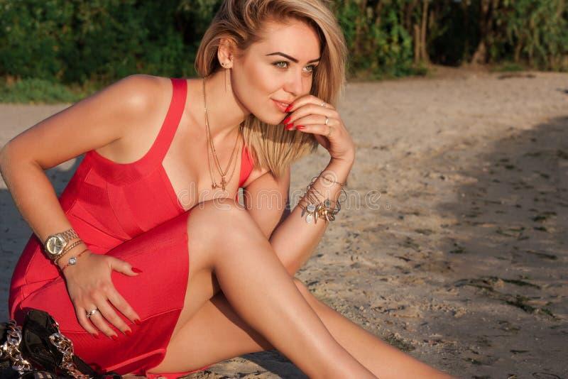 Blonde hermoso en un vestido rojo atractivo imágenes de archivo libres de regalías