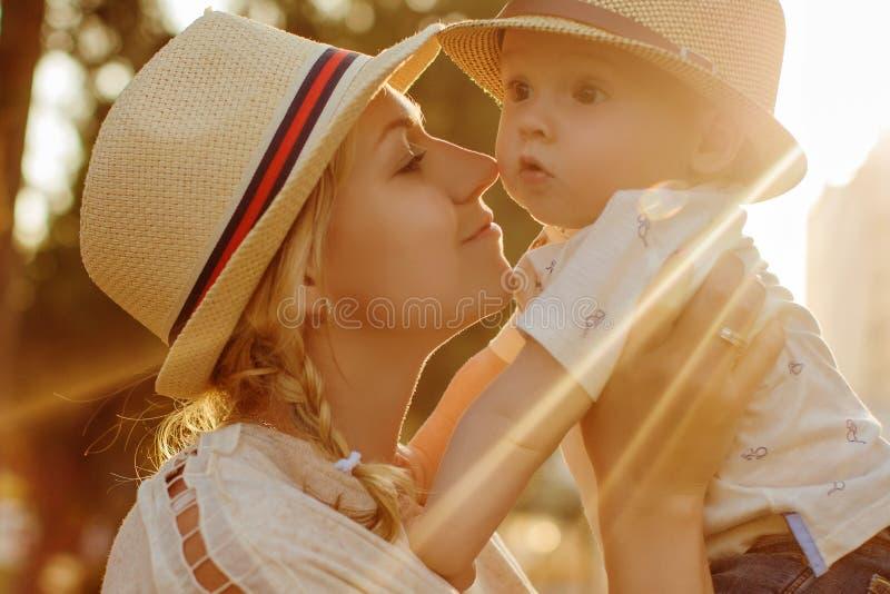 Blonde hermoso en una madre del sombrero que besa a su hijo en la puesta del sol en th fotografía de archivo