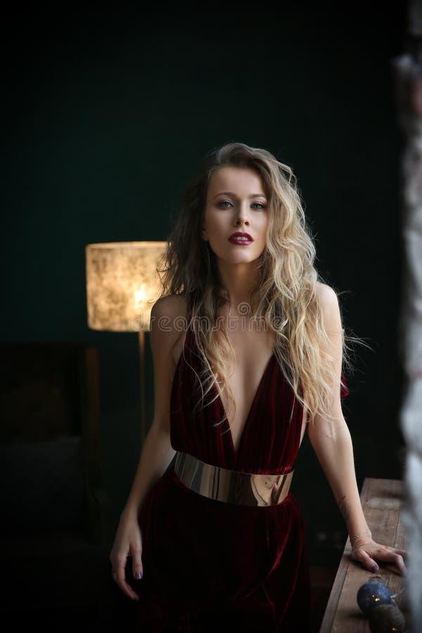 Blonde hermoso en vestido negro del terciopelo en fondo aristocrático del apartamento fotografía de archivo