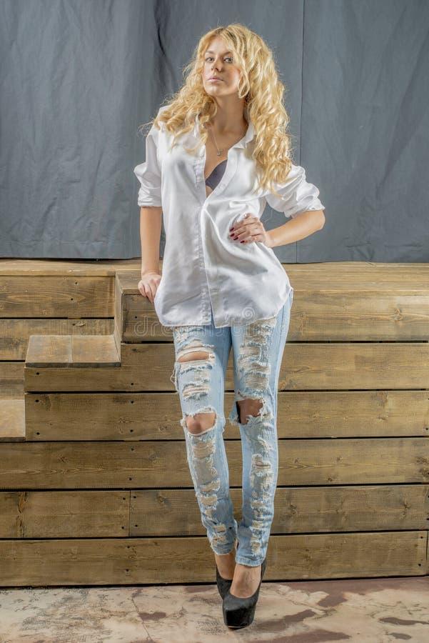 Blonde hermoso joven de la muchacha en una camisa blanca y vaqueros con huecos foto de archivo