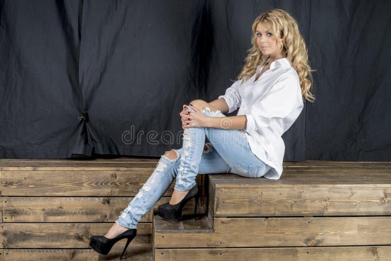 Blonde hermoso joven de la muchacha en una camisa blanca y vaqueros con huecos imagen de archivo