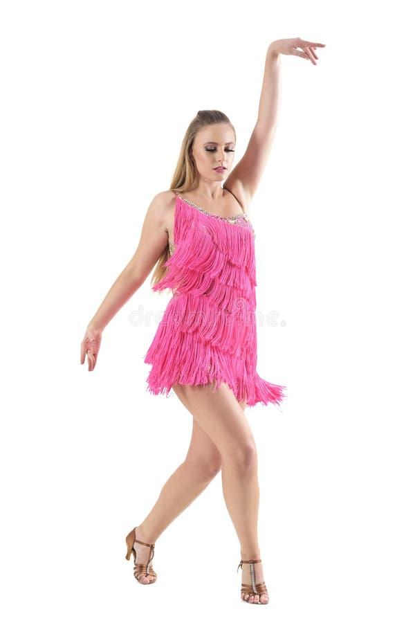 Blonde het bevallige Latino vrouwelijke danser stellen met wapen omhoog terwijl neer het kijken stock foto's