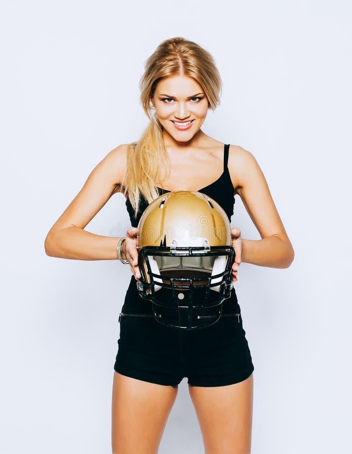 Blonde het stellen als Amerikaans voetbalmeisje op witte achtergrond Mooie jonge vrouw die zwarte uitrusting met Amerikaan dragen stock foto