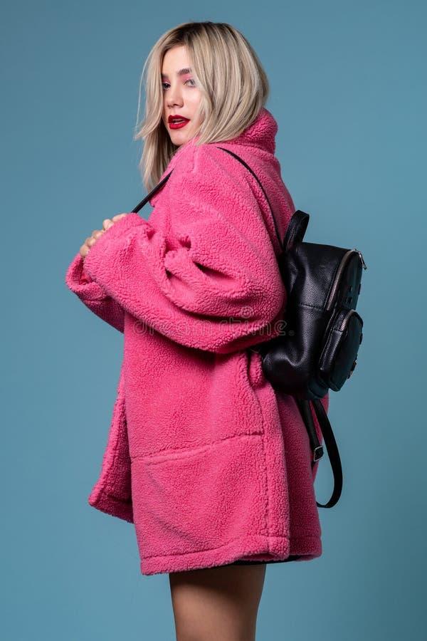 Blonde het vrolijke meisje stellen in modieuze roze laag in studio met zwarte rugzak stock fotografie