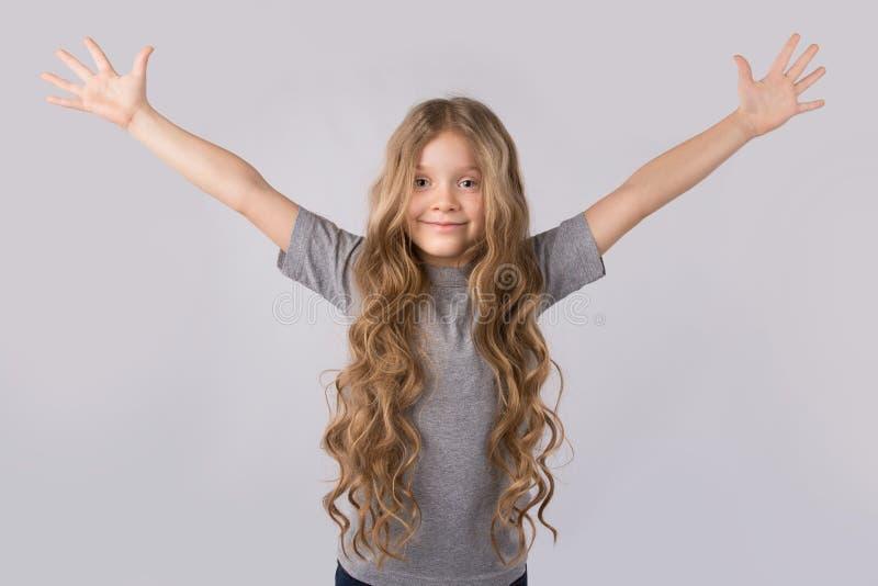 Blonde heureuse de petite fille avec de beaux cheveux d'isolement sur le fond blanc image libre de droits