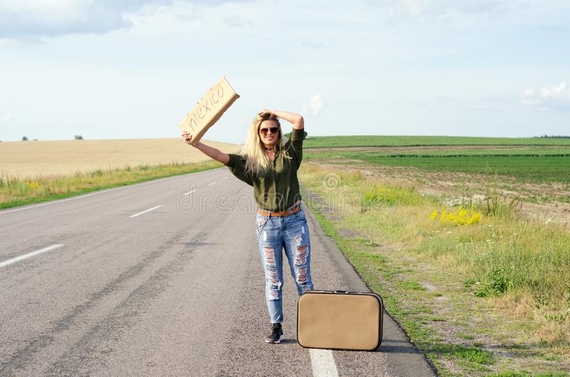 Beautiful Girl Hitchhiking On The Road Traveling. Blonde holding sign while hitchhiking on the road in summertime royalty free stock photo