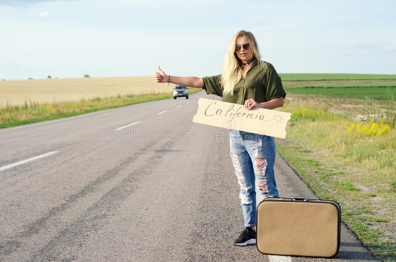 Beautiful Girl Hitchhiking On The Road Traveling. Blonde holding sign while hitchhiking on the road in summertime stock images