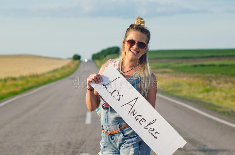 Beautiful girl hitchhiking on the road traveling. Blonde holding sign while hitchhiking on the road in summertime royalty free stock image