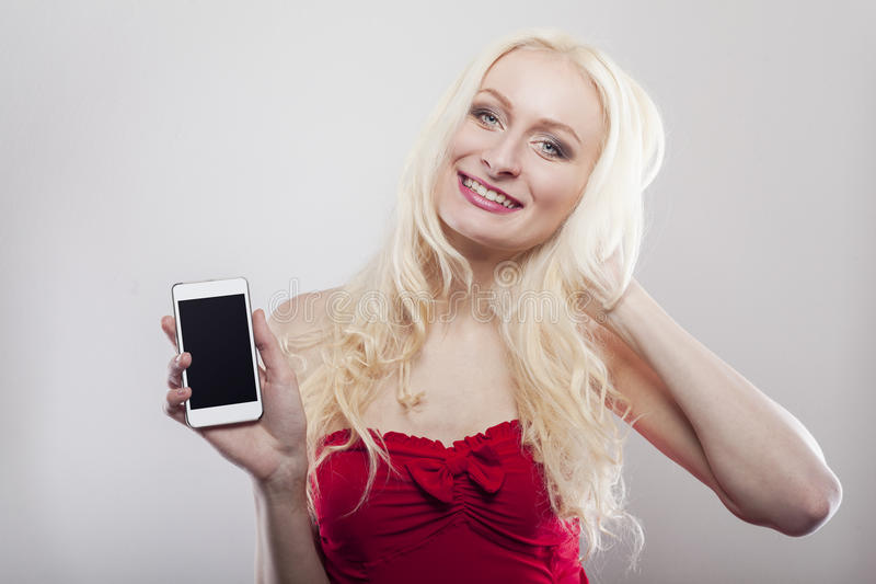 Blonde holding white cell phone in her hands royalty free stock image