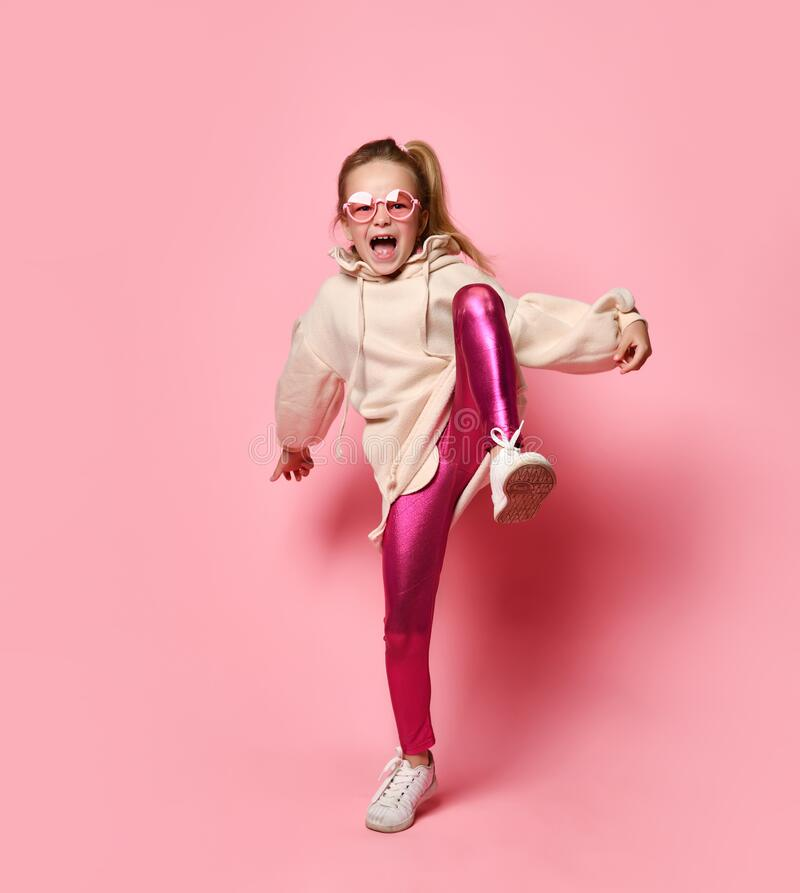 Blonde hooligan stomps her foot, sways in a pose, is indignant with screams, on a pink studio background. stock photo