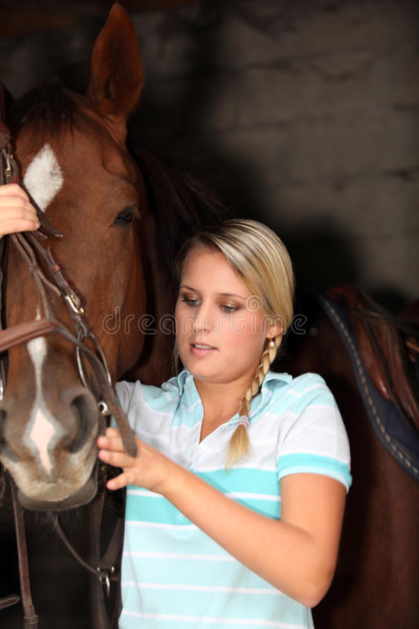 Blonde with horse. Young blond teenager stood with horse royalty free stock photo