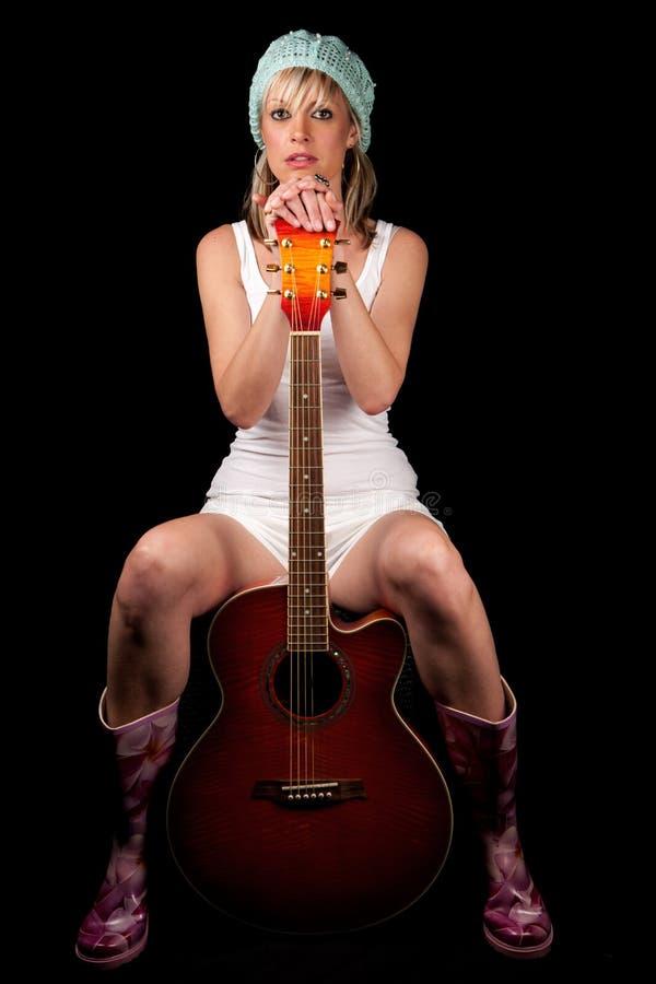 Blonde jonge volwassen musicus die haar gitaar houden stock foto