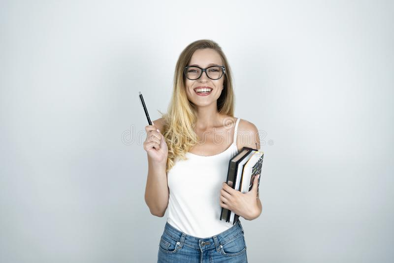 Blonde jonge vrouw die in glazen pen in één hand en boeken in haar houden andere hand die witte achtergrond glimlachen stock foto