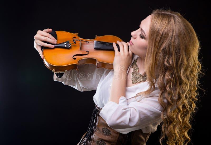Blonde jonge vrouw die viool bekijken royalty-vrije stock fotografie