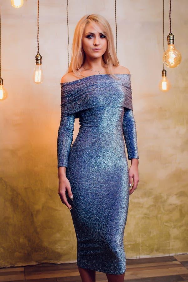 Blonde jonge vrouw in elegant blauw stock foto's