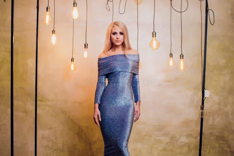 Blonde jonge vrouw in elegant blauw stock fotografie