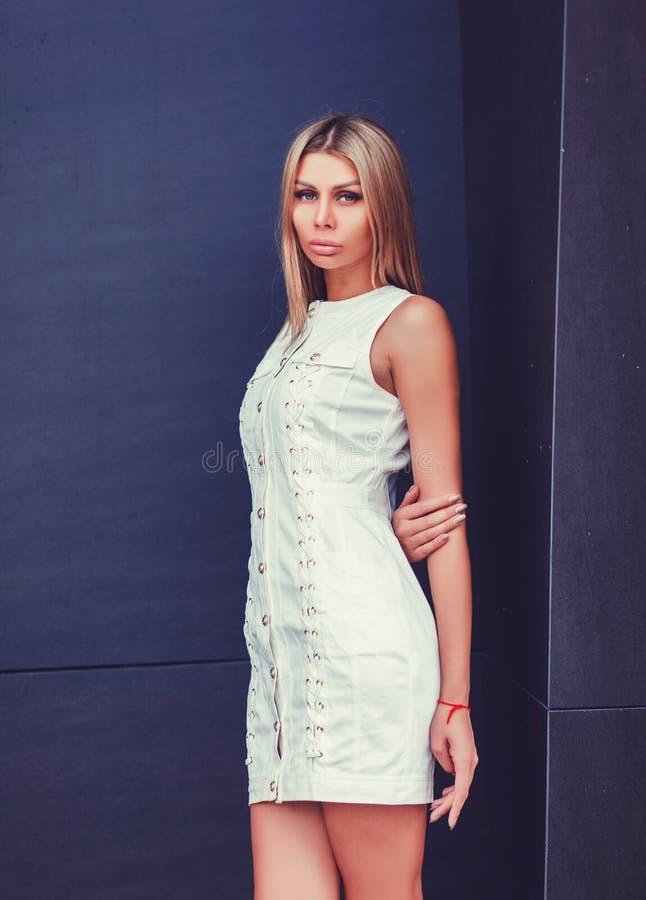 Blonde jonge vrouw in elegante witte kleding stock afbeelding
