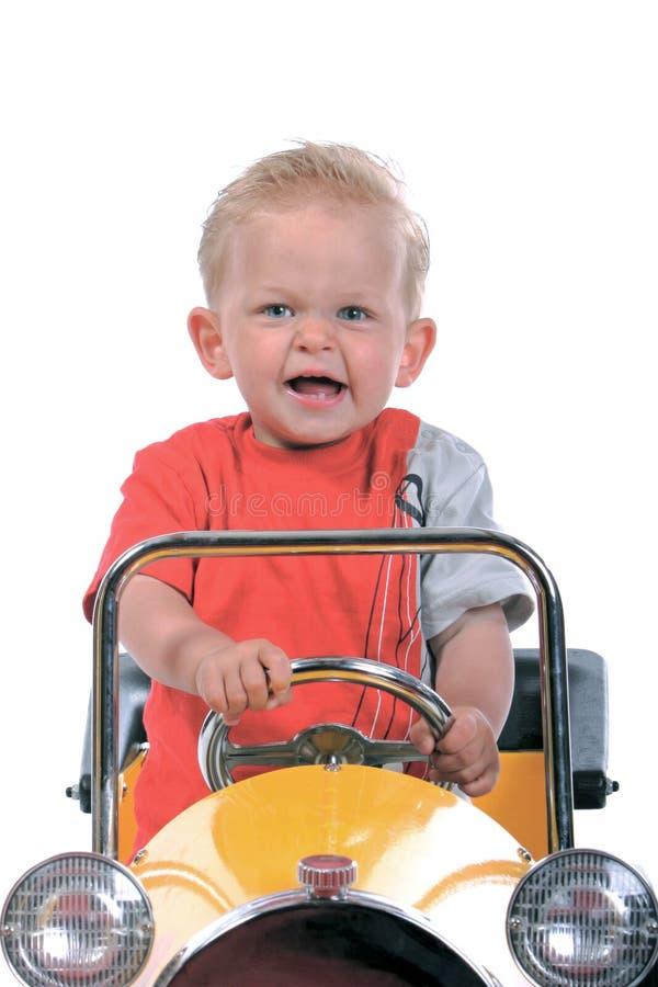 Blonde jongen die een stuk speelgoed auto drijft stock foto