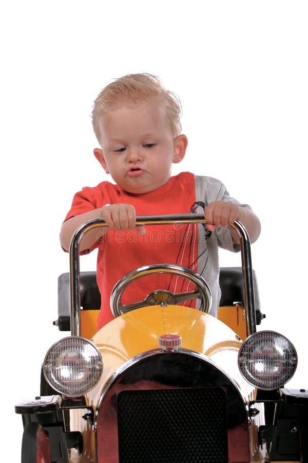 Blonde jongen die een stuk speelgoed auto drijft stock afbeelding