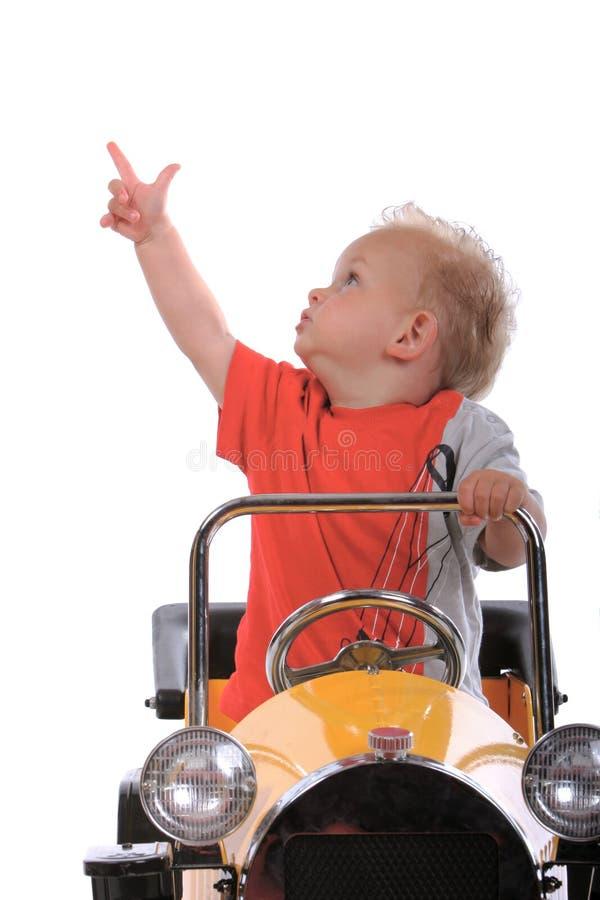Blonde jongen die een stuk speelgoed auto drijft stock fotografie