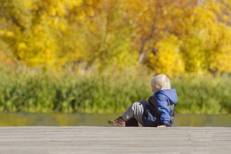 Blonde jongen in matrozenzitting op de rivierpijler Zachte nadruk royalty-vrije stock fotografie
