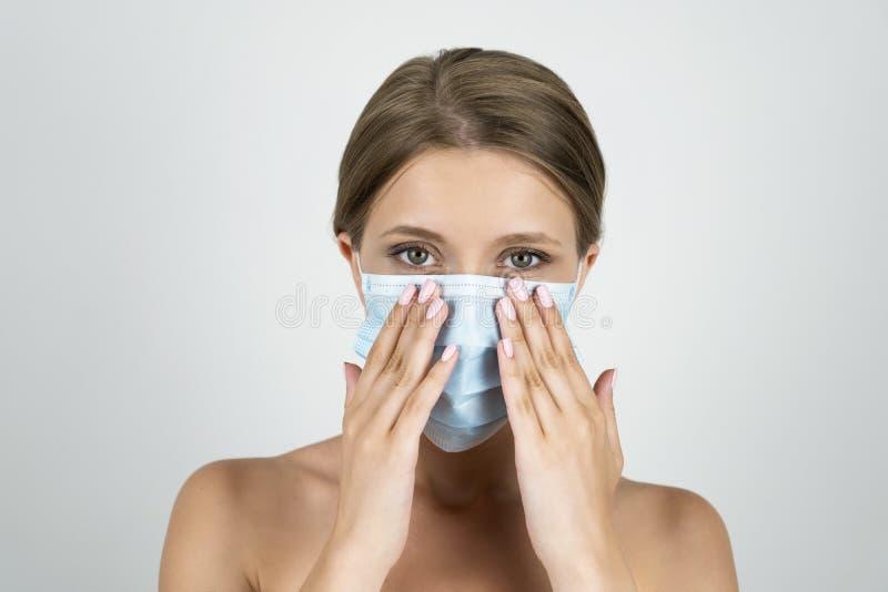 Blonde junge Frau, die medizinisches Maskenhändchenhalten nahe ihrem Gesichtsabschluß herauf lokalisierten weißen Hintergrund trä stockbilder