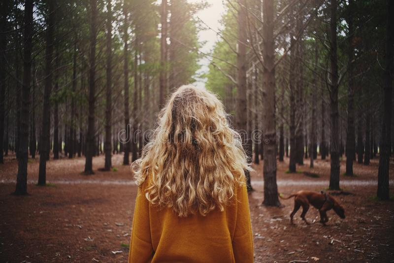 Blonde junge Frau mit ihrem Hund im Wald lizenzfreies stockfoto