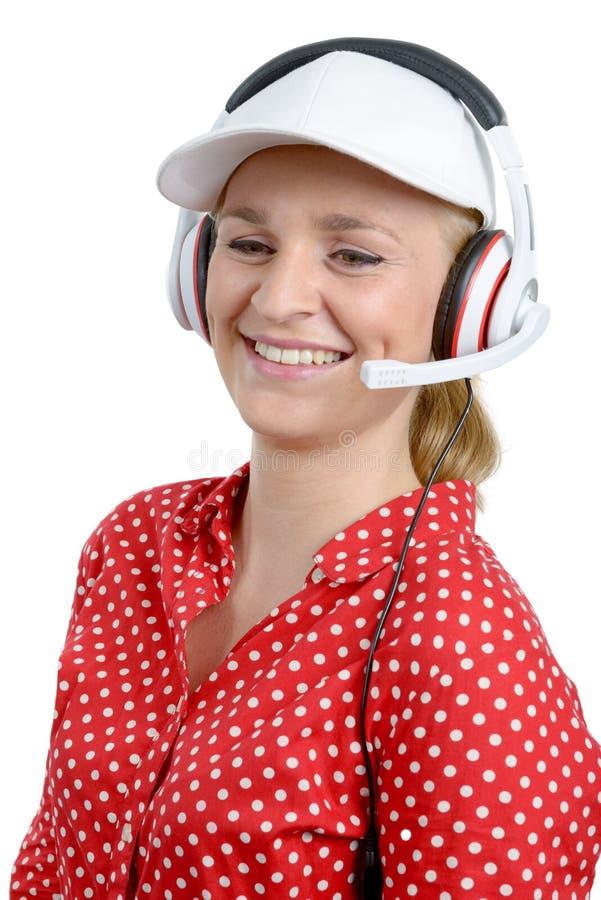 Blonde junge Frau mit Kopfhörer und weißer Kappe stockfoto