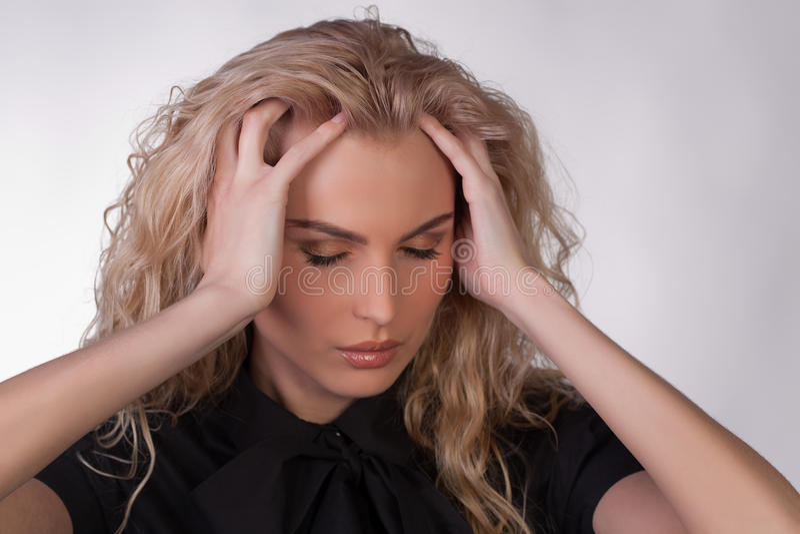 Blonde junge Frau mit Kopfschmerzen stockfotografie