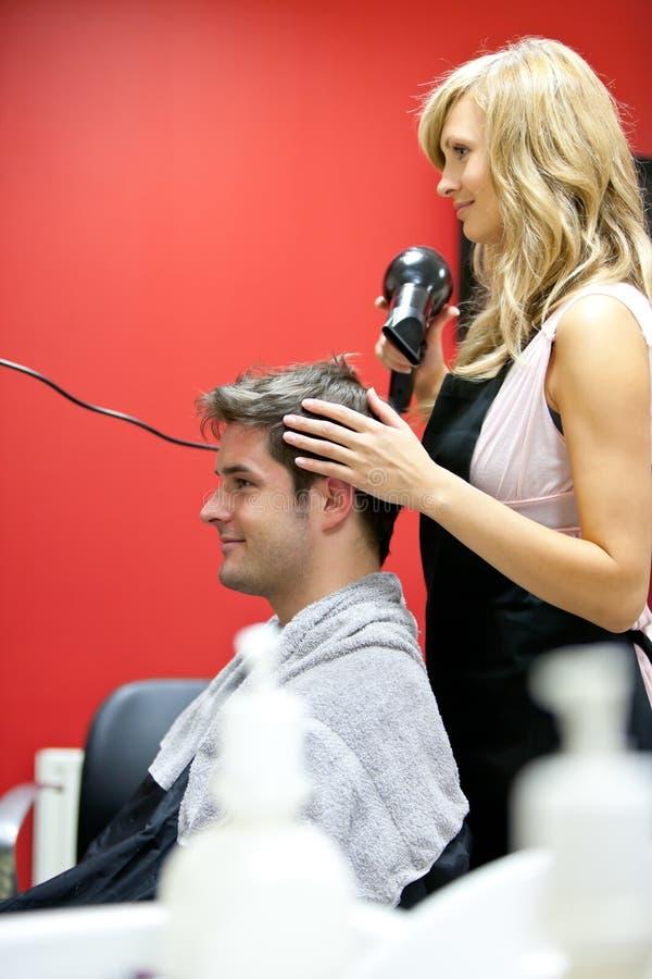 Blonde kapper het drogende haar van haar klant stock afbeeldingen