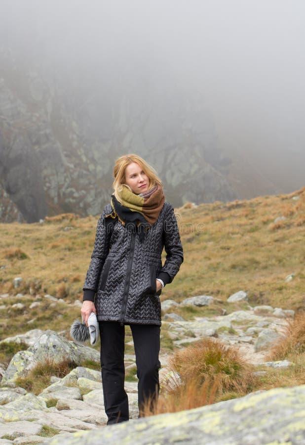 Blonde kaukasische Frau, die in der Gebirgsnatur aufwirft lizenzfreies stockbild