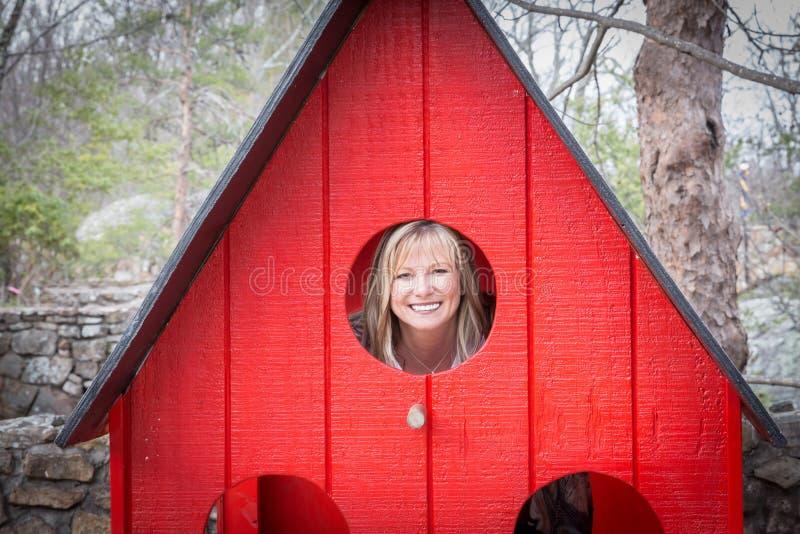 Blonde kaukasische Frau, die durch ein kleines Fenster emporragt lizenzfreie stockbilder
