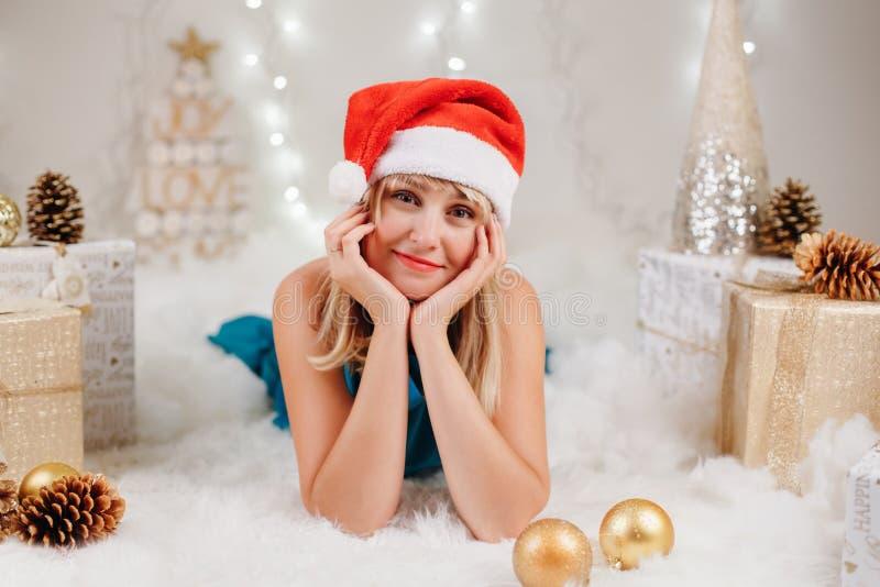 Blonde kaukasische junge Frau mit braunen Augen in Weihnachtsmann-Hut Weihnachten feiernd lizenzfreie stockfotografie